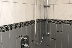 Custom tiled shower with mosaic accent tile